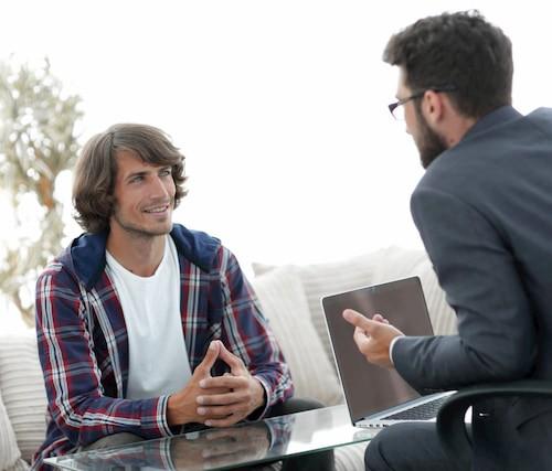 deux hommes discutant devant une table basse